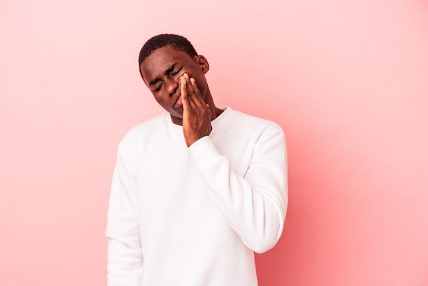 強い歯の痛み、臼歯の痛みを持っているピンクの背景に分離された若いアフリカ系アメリカ人の男。