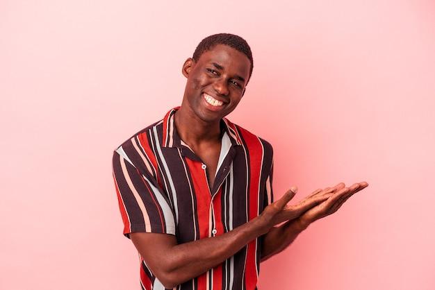 手のひらにコピースペースを保持しているピンクの背景に分離された若いアフリカ系アメリカ人の男。