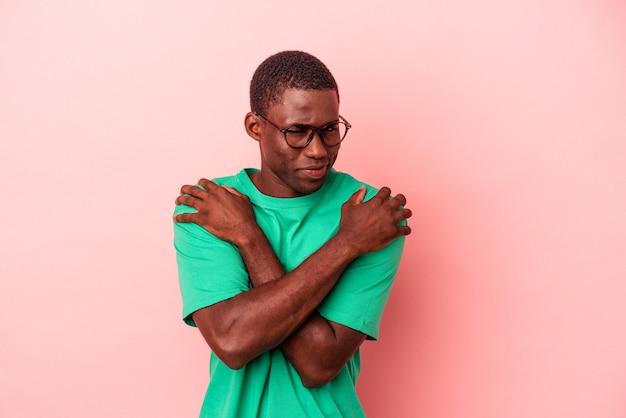 ピンクの背景に孤立した若いアフリカ系アメリカ人の男は、のんびりと幸せに笑って抱擁します。