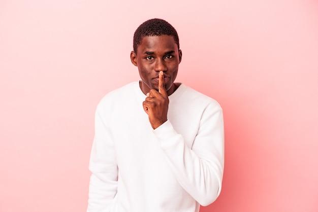 秘密を守るか、沈黙を求めてピンクの背景に孤立した若いアフリカ系アメリカ人の男。