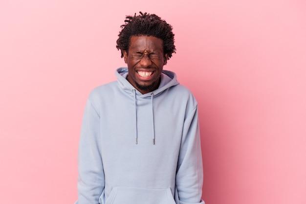 ピンクの背景に孤立した若いアフリカ系アメリカ人の男は笑って目を閉じ、リラックスして幸せな気分になります。