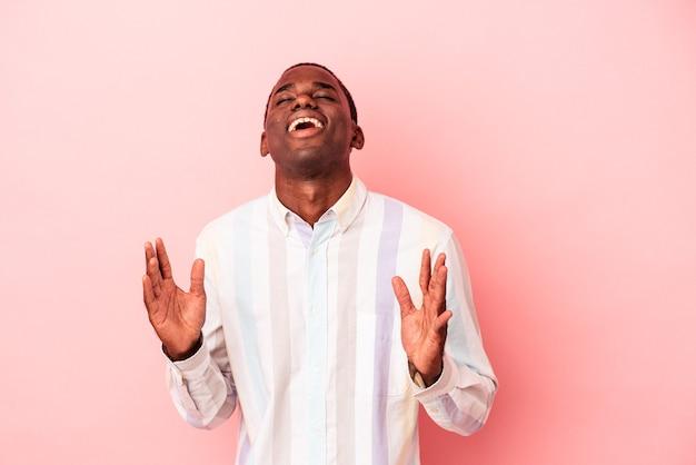 ピンクの背景に孤立した若いアフリカ系アメリカ人の男は、胸に手を置いて大声で笑います。