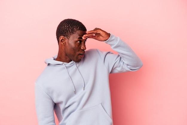 額に手を置いて遠くを見ているピンクの背景に孤立した若いアフリカ系アメリカ人の男。