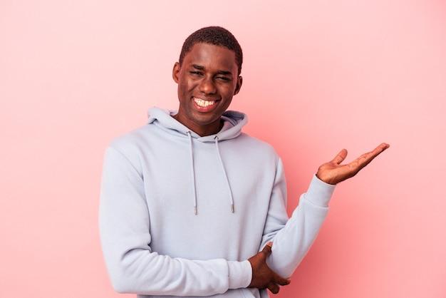 ピンクの背景に孤立した若いアフリカ系アメリカ人の男性は、手のひらにコピースペースを示し、腰に別の手を保持しています。