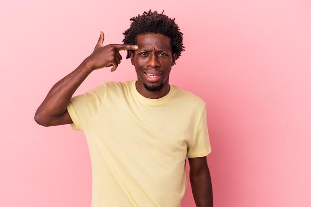 人差し指で失望のジェスチャーを示すピンクの背景に分離された若いアフリカ系アメリカ人の男。