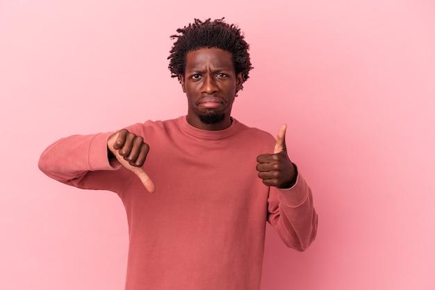 親指を上と親指を下に示すピンクの背景に分離された若いアフリカ系アメリカ人の男、難しい選択の概念