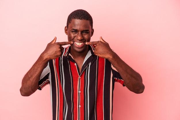 ピンクの背景の笑顔で孤立した若いアフリカ系アメリカ人の男は、口に指を指しています。