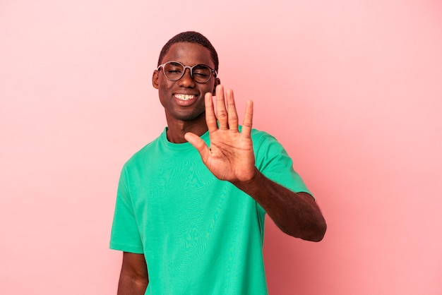 ピンクの背景に孤立した若いアフリカ系アメリカ人の男は、指で5番を示して陽気な笑顔を浮かべています。