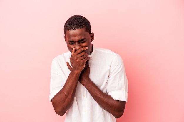 ピンクの背景に分離された若いアフリカ系アメリカ人男性は、ウイルスや感染症のために喉の痛みに苦しんでいます。