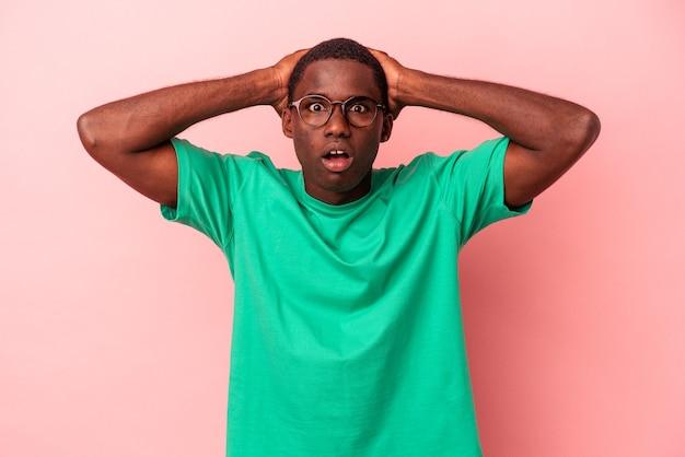 ピンクの背景に孤立した若いアフリカ系アメリカ人の男は驚いてショックを受けました。