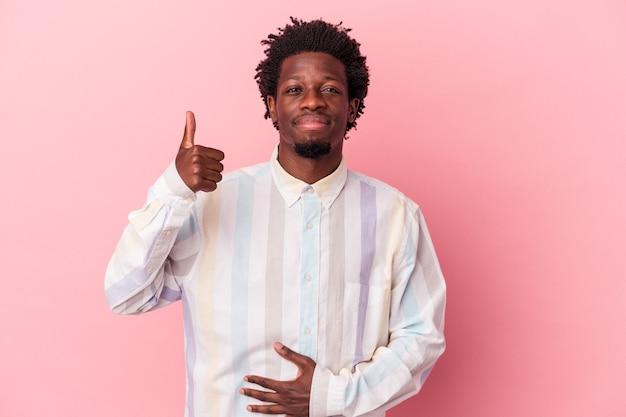 ピンクの背景に分離された若いアフリカ系アメリカ人の男は、おなかに触れ、優しく微笑んで、食事と満足の概念。