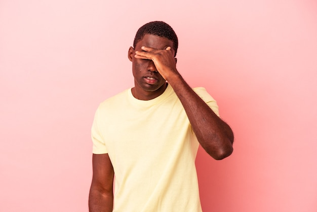 寺院に触れて頭痛を持っているピンクの背景に孤立した若いアフリカ系アメリカ人の男。