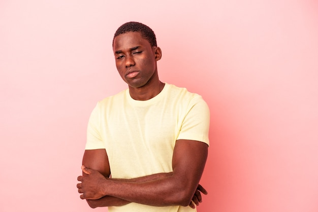 皮肉な表情でカメラを見て不幸なピンクの背景に孤立した若いアフリカ系アメリカ人の男。
