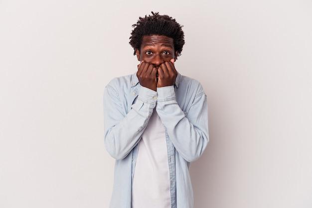 若いアフリカ系アメリカ人の男性は、白い背景に爪を噛んで孤立し、神経質で非常に心配しています。