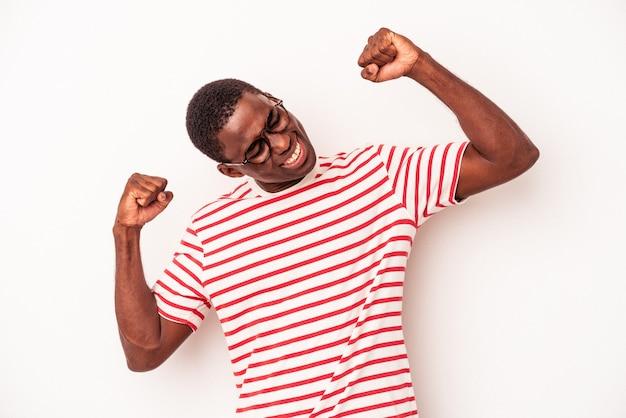 特別な日を祝う白い背景に孤立した若いアフリカ系アメリカ人の男は、エネルギーでジャンプして腕を上げます。