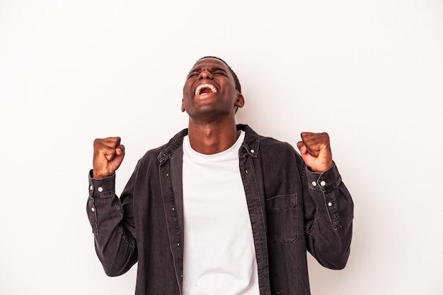 勝利、情熱と熱意、幸せな表現を祝う白い背景に孤立した若いアフリカ系アメリカ人の男。