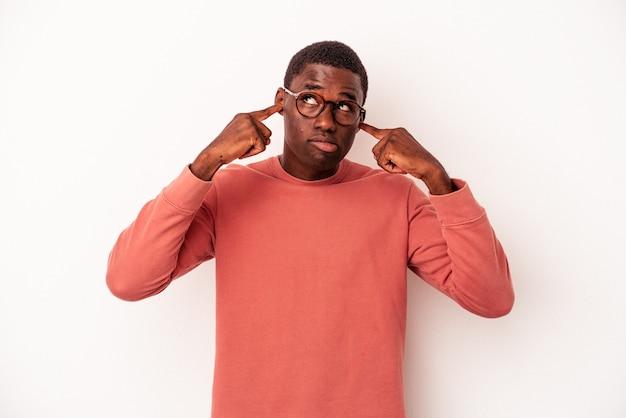 指で耳を覆っている白い背景に孤立した若いアフリカ系アメリカ人の男は、大声で周囲によってストレスと必死になりました。