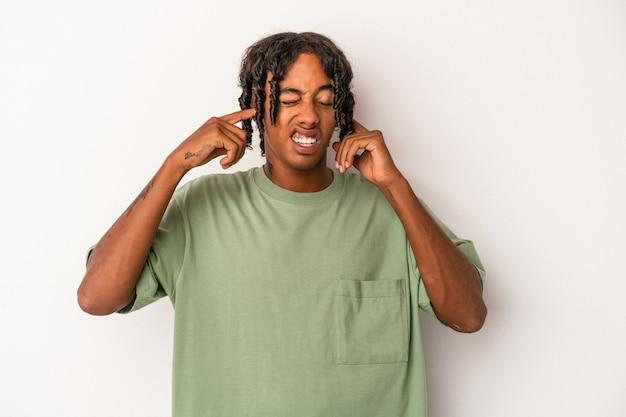 指で耳を覆う白い背景で隔離された若いアフリカ系アメリカ人の男は、大声で周囲によってストレスと必死になりました。