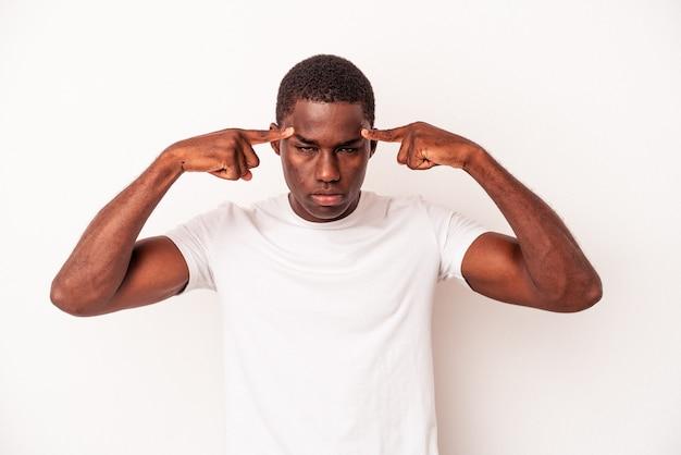 흰색 배경에 격리된 젊은 아프리카계 미국인 남자는 집게손가락으로 머리를 가리키는 작업에 집중했습니다.