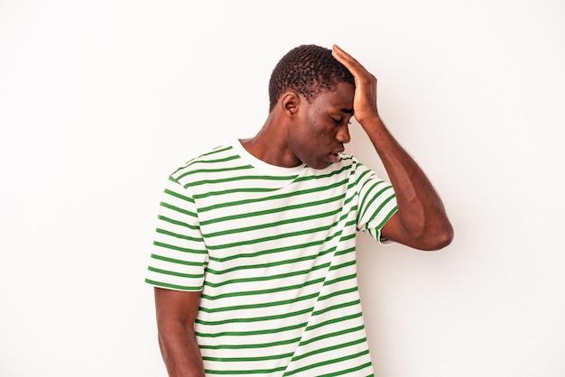 何かを忘れて、手のひらで額を叩き、目を閉じて、白い背景で孤立した若いアフリカ系アメリカ人の男。