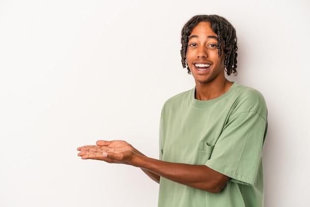 手のひらにコピースペースを保持している白い背景で隔離の若いアフリカ系アメリカ人の男。