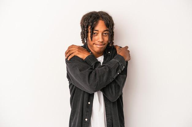白い背景の抱擁に分離された若いアフリカ系アメリカ人の男は、のんびりと幸せに笑っています。