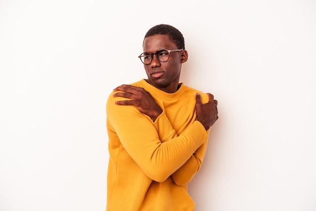 白い背景で隔離の若いアフリカ系アメリカ人の男は、のんびりと幸せに笑って抱擁します。