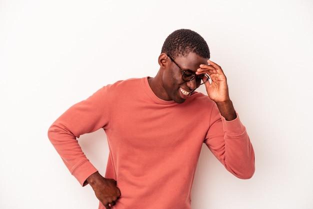 たくさん笑ってうれしそうな白い背景に孤立した若いアフリカ系アメリカ人の男。幸福の概念。
