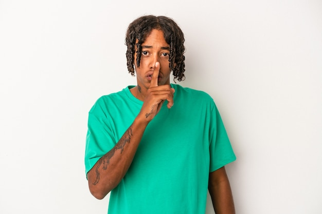 秘密を保持するか、沈黙を求めて白い背景で隔離の若いアフリカ系アメリカ人の男。