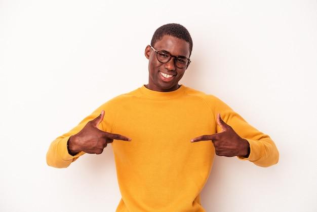 白い背景で隔離の若いアフリカ系アメリカ人の男は、指で下向き、前向きな気持ちです。