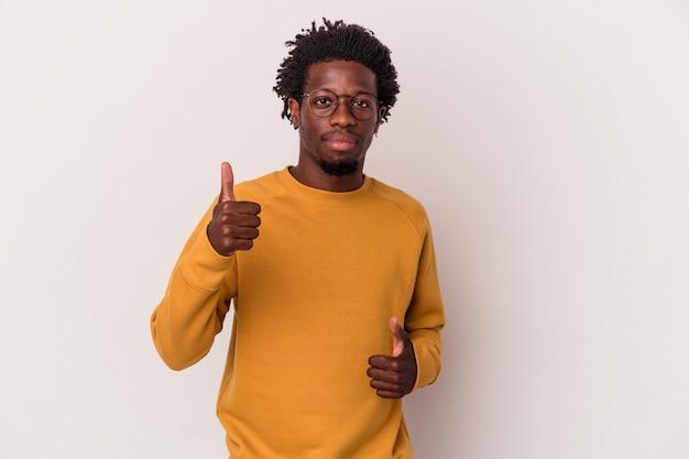 若いアフリカ系アメリカ人の男性は、白い背景に孤立し、両方の親指を上げて、笑顔で自信を持っています。