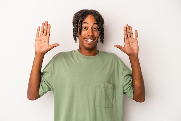 白い背景に孤立した若いアフリカ系アメリカ人の男は、嬉しい驚きを受け取り、興奮し、手を上げます。