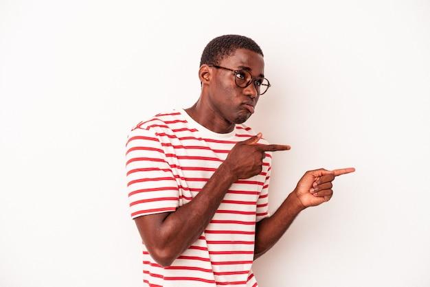 Молодой афро-американский мужчина, изолированные на белом фоне, потрясен, указывая указательными пальцами на копию пространства.