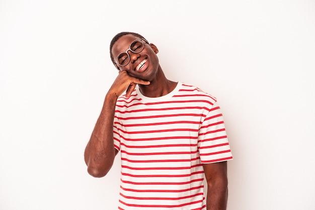 指で携帯電話の呼び出しジェスチャーを示す白い背景で隔離の若いアフリカ系アメリカ人の男。