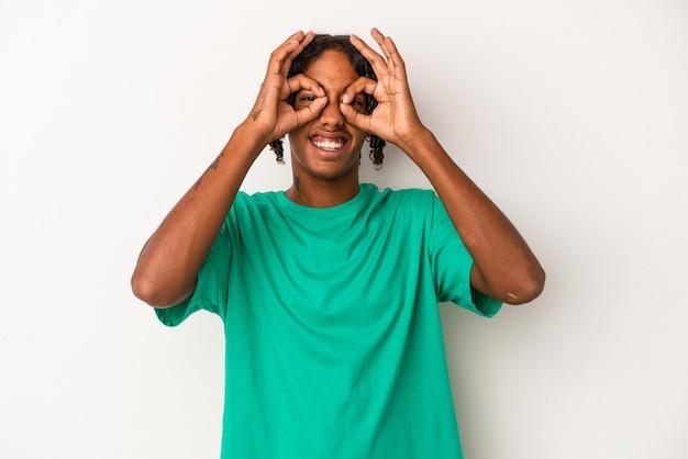 目の上に大丈夫サインを示す白い背景で隔離の若いアフリカ系アメリカ人の男