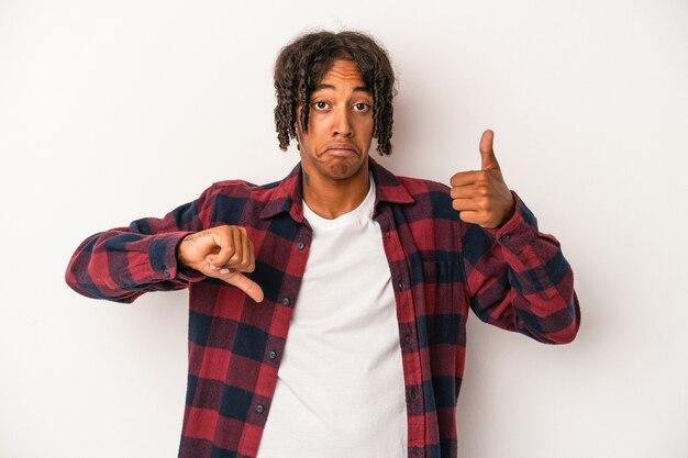 親指を上と親指を下に示す白い背景で隔離の若いアフリカ系アメリカ人の男、難しい選択の概念