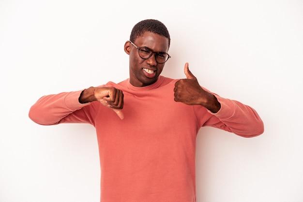 親指を上に、親指を下に、難しい選択の概念を示す白い背景で隔離の若いアフリカ系アメリカ人の男