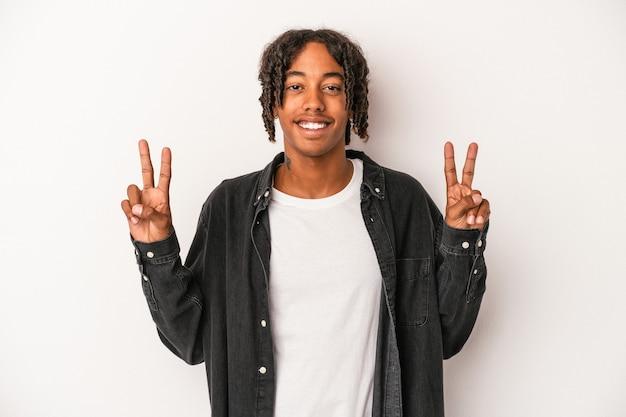 勝利のサインを示し、広く笑顔の白い背景で隔離の若いアフリカ系アメリカ人の男。