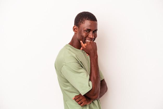 若いアフリカ系アメリカ人の男は、手であごに触れて、幸せと自信を持って笑顔の白い背景で隔離。