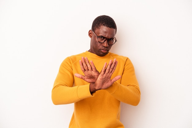 一時停止の標識を示す伸ばした手で立っている白い背景に孤立した若いアフリカ系アメリカ人の男は、あなたを妨げています。