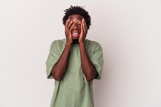若いアフリカ系アメリカ人の男は、白い背景で孤独に泣き叫びながら孤立しました。