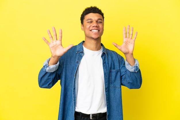 Молодой афро-американский мужчина изолирован на желтом фоне, считая десять пальцами