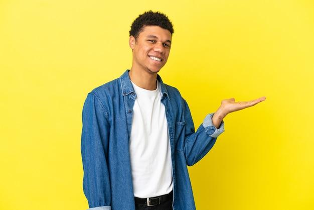 Молодой афроамериканец, изолированный на желтом фоне, держит воображаемое пространство на ладони, чтобы вставить объявление