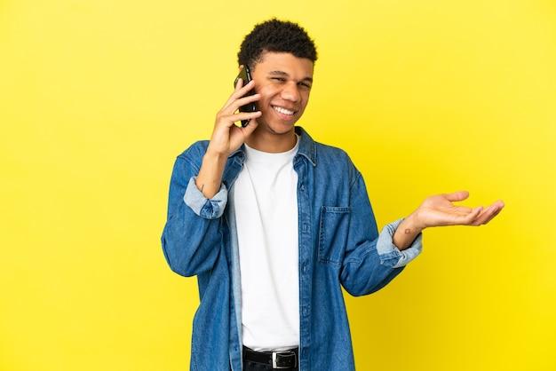 Молодой афроамериканец, изолированные на желтом фоне, разговаривает с кем-то по мобильному телефону