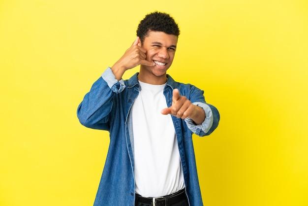 Молодой афро-американский мужчина изолирован на желтом фоне, делая жест по телефону и указывая вперед