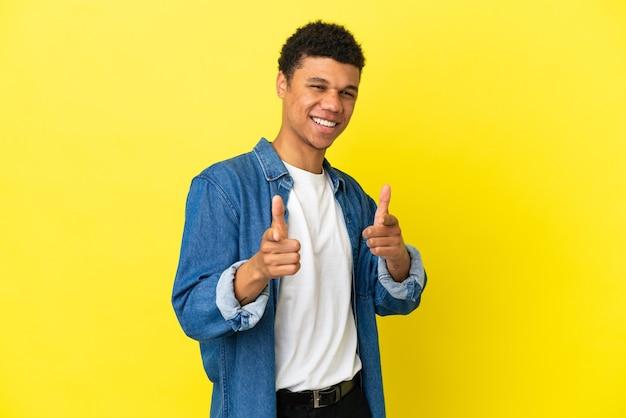 Молодой афро-американский мужчина изолирован на желтом фоне, указывая вперед и улыбается