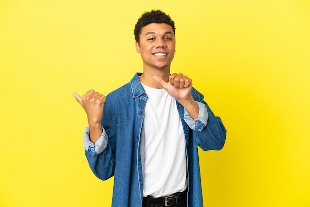 Молодой афро-американский мужчина изолирован на желтом фоне, указывая в сторону, чтобы представить продукт