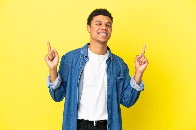 Молодой афро-американский мужчина изолирован на желтом фоне, указывая на отличную идею