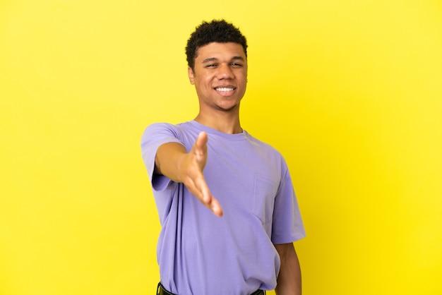 Молодой афро-американский мужчина изолирован на желтом фоне, пожимая руку для заключения хорошей сделки