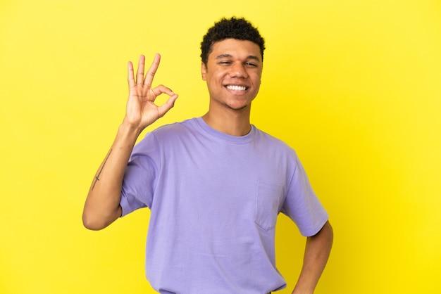 Молодой афроамериканец, изолированные на желтом фоне, показывает пальцами знак ок